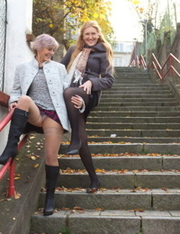 Mature lesbians flash upskirts on stairs while walking out in public