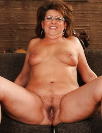 Naughty granny in glasses undressing and spreading her legs